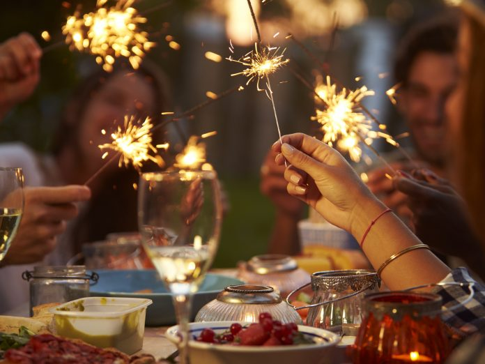 Friends With Sparklers Eating Food And Enjoying Party at Geneva-on-the-Lake