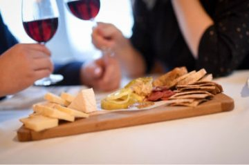 couple drinking wine in front of cheese plate