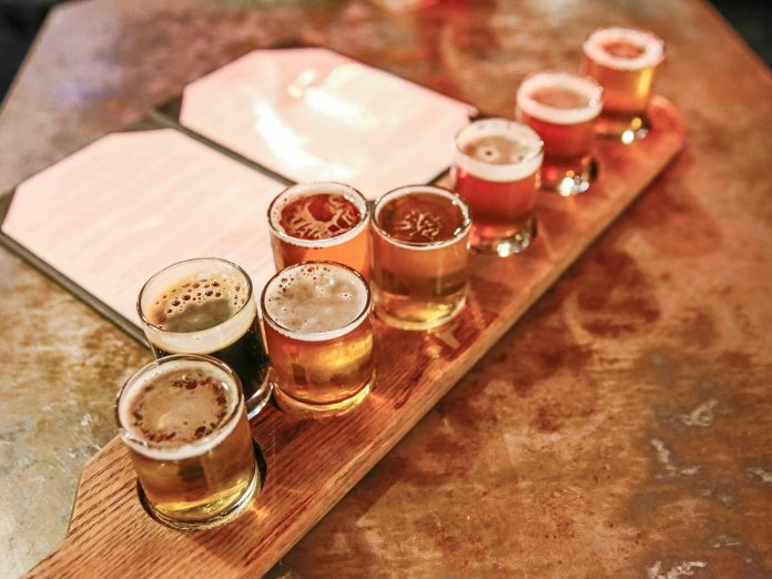 Craft beers in taster glasses are lined up for a beer tasting flight on a bar counter in a northeast ohio brewery.