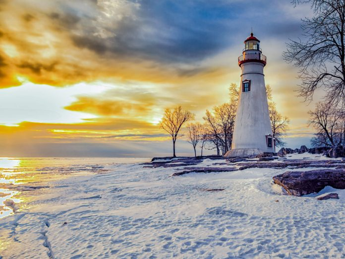 marblehead lighthouse at sunrise, with sand and the lake erie shores. marblehead lighthouse is one of lake erie ohio's oldest lighthouses.