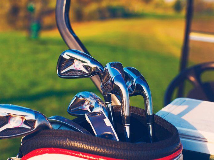 A set of clubs on the back of a golf cart on a green golf course in Northeast Ohio.