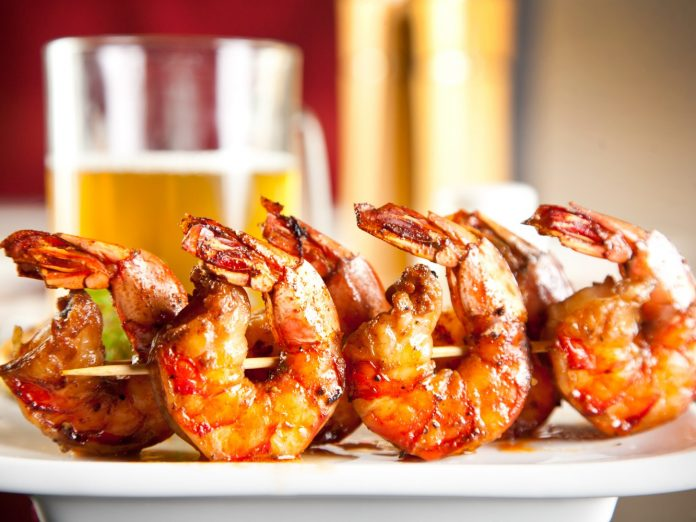 A plate of grilled shrimp with a glass of beer in the background at a restaurant in Ashtabula, Ohio.