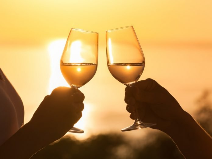 a couple holding wine glasses with a lake erie sunset in the background.