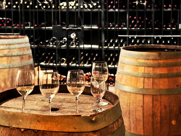 Row of wine glasses on barrel in winery cellar on a wine tour in Geneva-on-the-Lake, Ohio.